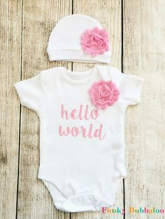 An adorable outfit for any new born baby girl! This Hello World bodysuit is great for newborn photo shoots or a baby shower gift. The bodysuit is 100% cotton, embellished with high quality vinyl and a chiffon flower for a fancy finish! With a matching soft cotton hat. Our Hello World design comes in a variety of colour options - but if you want a colour that isnt listed - just get in touch! We can usually accommodate! Please see our other items for alternative colours.  How to order: 1…