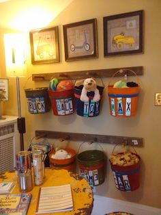 {photo only} Peg Rack, metal buckets with cut up license plates as labels= Toy storage.