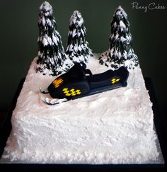 Snowmobile Cake - Birthday Cake for my bro, complete with a replica of his sled (fondant) and edible trees! ..Dark Chocolate Fudge cake with Peanut Butter filling and Buttercream icing. The trees are sugar cones with icing piped on, dusted with powdered sugar.