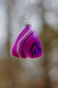 This is a beautiful triangle agate stone pendant. Sterling silver hand wrapped wire attaches to a sterling silver chain. The pendant is 2 (7.5cm) long and 1.5 (4cm) wide. The light shines through the stone accentuating the beautiful purple and white coloured dragon veins in the striking