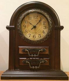 Espetacular relógio de mesa em madeira nobre belamente torneada e detalhes em metal com bordados fenestrados duas gavetas medindo 35 cm de altura por 26 cm de largura e 11 cm de profundidade.
