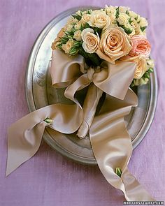 tight dome of roses w/ satin bow and buds sewn into ribbon ends