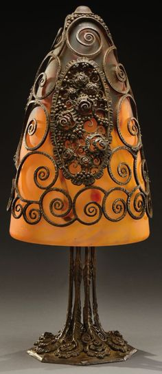 """EDGAR BRANDT & DAUM NANCY, A rare and exceptional hammered wrought iron desk lamp composed of eight stalks ending in stylised coiling plant elements and surmounted by a marbled glass shade held in a wrought iron netting with a cartouche decorated with stylized flowers. Engraved stamp signature """"E.Brandt"""" and """"Daum Nancy"""". Circa 1925. H : 19 ¾ in:"""