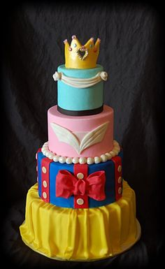 A cake that represents the Princess Dresses. Starting from the Bottom: Belle, Snow White, Sleeping Beauty and Cinderella with a gumpaste crown on top.