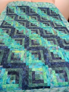 This beautiful quilt top was machine pieced, pressed, squared up and ready to be quilted. We used 5 different blue, purple and jade tone batik fabrics. Iris in jade tone was used for the borders. It i
