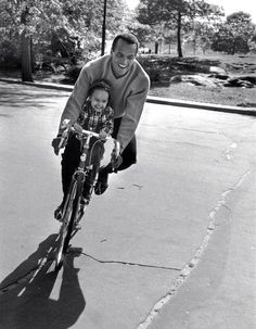 Harry and Shari Belafonte ride a bike.