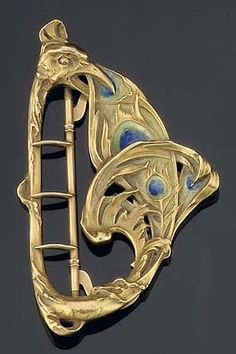 AN ART NOUVEAU ENAMEL BUCKLE, BY L. GAUTRAIT. The gold buckle of stylised peacock design with blue and green enamel, French mark for gold, circa 1890. Signed L. Gautrait. #ArtNouveau #Gautrait #buckle