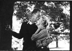 O escritor Arthur Miller beija na testa a mulher Marilyn Monroe à sombra de uma árvore da sua quinta, logo a seguir ao casamento