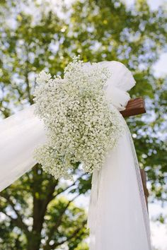 wooden ceremony arch with sheer white fabric and cluster of baby's breath                                                                                                                                                                                 More