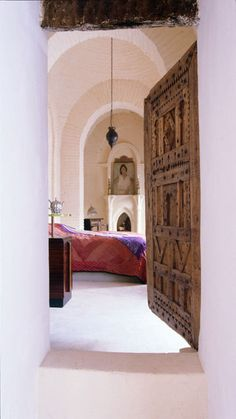 A fabulous carved Moroccan Berber door leads to a bedroom with cascading arches.