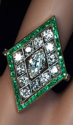 1920s finely crafted platinum topped 14K gold ring is centered with a prong-set sparkling old marquise cut diamond, framed by 12 bright white old European and transitional cut diamonds, and bordered by numerous channel-set calibre cut emeralds. The shoulders of the ring are embellished with a pair of baguette cut diamonds. Estimated total diamond weight 1.60 cts.
