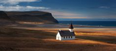 Breidavik, Iceland:  In the Northwest corner of Iceland, the West Fjords is a remarkable location for isolated landscapes. This church stands watch above a golden sand beach with barely a town near by.