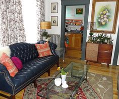 eclectic living room: navy chesterfield sofa paired with chrome and glass coffee table, layered rugs, floral drapes and art and mid century modern record console