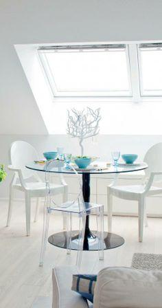 Kattoikkuna valaisee pöytäryhmää. Philippe Starck on yksi Piitan lempisuunnittelijoista. T-Table ja Louis Ghost -muovituolit tuovat pyöreän muodon kulmikkaitten kattojen rinnalle. | Valon vintti | Koti ja keittiö