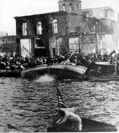 Cosmopolitan Smyrna burns in the background as refugees desperately board boats to flee the massacre which ensued