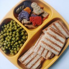 Grilled cheese sandwich, Annie's Homegrown Animal Cookies (colored with fruit and vegetable extracts), My Super Foods Company Organic Blueberry Vanilla Cookies, and peas.