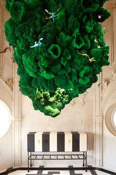 Surreal light fixture by Ingo Maurer. A 12-foot-high hanging mass of emerald-green sponges, glowing from within thanks to hidden L.E.D.'s.