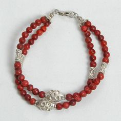 """Handmade gemstone coral bracelet features 2 strands of semi-precious red coral gemstones, sterling silver accent beads, lobster claw clasp and wire band. 7 1/2"""" in length. Add a necklace, pendant and"""