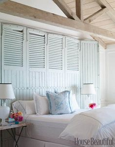 To add a beachy-vibe to her crisp, white bedroom, designer Carolyn Espley-Miller hung an old sea-foam barn door above her bed.