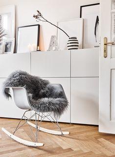 Was für ein schönes Plätzchen! Der Schaukelstuhl ist wohl der Hingucker im Raum und dazu noch der Beliebteste. Die Mischung aus Kunststoff, Metall und Buchenholz ergibt das erfrischende und klassische Design für einen ,,All time favorite''. Das kuschelige Schaffell Carry sorgt zusätzlich für Komfort und flauschige Entspannung! // Schaukelstuhl Wohnzimmer Sideboard Styling Ideen Skandinavisch Fell #WohnzimmerIdeen #Skandinavisch