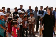 Actress Angelina Jolie (right) smiles at Syrian refugee children after a news…