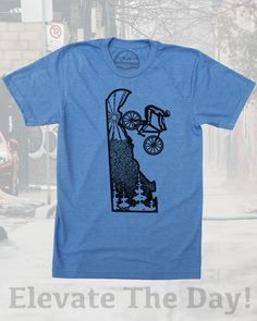 Delaware home shirt with mountain bike graphic by Milostees- Original Illustration of a cyclist descending the Diamond State for an epic ride. Hand screen printed image on soft cotton, polyester apparel that is great for bike rides at White Clay Creek or casual wear watching Blue Hen games. Elevate the day wear a more comfortable you! $21.99, free shipping in the USA!  #Delaware #DelawareShirt