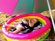 Keep baby in an inflatable pool at the beach to keep him semi-protected and from sand in his mouth and diaper