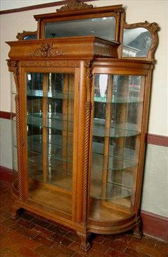 Found on EstateSales.NET: 2 - Large oak curved glass china cabinet with lion heads in crown, top mirror panel, glass shelves and  claw feet.