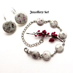 Delicate Handmade Item  * Material: Real crushed heather and lavender flowers in white  Eco-Resin set in platina plated bracelet.     *The Earrings are silver plated     This jewellery set is nickel and lead free.    * Size:  The Bracelet is 23cm long and  12mm wide cabochons.  Earrings are 2cm wide     This Unique, Exquisite and Distinctive Jewellery Set Will Make You Stand Out From The Crowd! A Fabulous Treat For Yourself Or a Gift For Someone Special!     Gift bag:  The Set Jewellery…