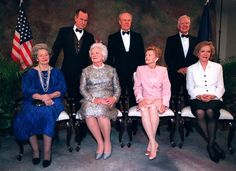 President George Bush gives his wife, Barbara the old rabbit ears during a formal portrait with other past presidents Gerald Ford, center, and Jimmy Carter at right. In the front row left to right, are Lady Bird Johnson, Barbara Bush, Betty Ford and Rosalynn Carter. The group was getting ready to attend a dinner in honor of Gerald Ford on April 16, 1997, the day before the re-dedication of his museum