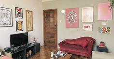 Sala de estar com piso de madeira e sofá vermelho