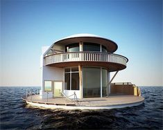 Round, two story house in the middle of the ocean. Second floor balcony and first floor deck