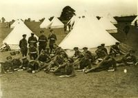 """Ireland, Civil War: """"A group of Irish Free State Army soldiers reclining on the found outside tents and eating a meal; some are standing and others are moving around in the background (Date stamped 18 July)."""" UCD Digital Library, Desmond FitzGerald Photographs, Photograph by W.D. Hogan."""