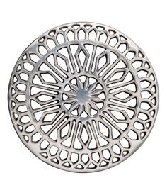 Silver-colored. Metal trivet with a perforated pattern and round feet. Diameter 6 1/2 in.