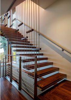 Escada suspensa em madeira e metal. Corrimão de metal e cabos.