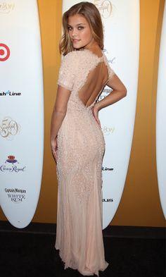 Nina Agdal powder pink long dress with open back detail.
