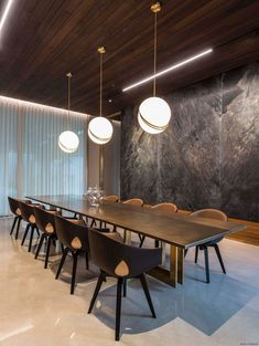 In this modern dining room, three pendant lights hang above a large dining table, while stone slabs are featured on the wall. #DiningRoom #LargeDiningTable