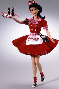"""1999. Pop Culture. COCA-COLA Barbie Series.Coca-Cola Barbie Doll (Brunette Waitress). COKE red and white uniform with matching gingham print trim. COCA-COLA trademarks adorning her apron, waitress cap and """"bottle-top"""" serving tray. Front of her uniform sports a Barbie monogram and cute little attached gingham print hankie. Wears black and white saddle shoes. Writing tablet. Brunette version available exclusively at Disney World Orlando, Florida."""