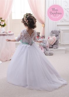 This gorgeous ballgown features a sheer lace neckline, fitted lace bodice with half-length sleeves, and full tulle skirt. Unique detailing includes contrasting sash with a front bow, and an elegant V-cut back that zips up under corset lace-up. Tulle Flower Girl, Tulle Flowers, Flower Dresses, Flower Girls, Flower Girl Hair Accessories, Silver Accessories, Violet Dresses, First Communion Dresses, Bridesmaid Dresses