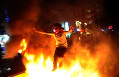 A Turkish boy jumps through fire during clashes in the Gazi district of Istanbul on June 11, 2013. (Bulent Kilic/AFP/Getty Images)