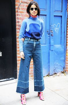 Leandra Medine of the Man Repeller wearing a sweater tucked into wide-leg jeans, and printed boots