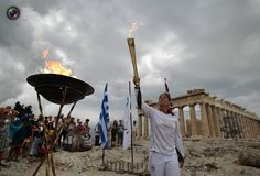 Greek athlete Niki Liosi lights her Olympic torch from a cauldron with the Olympic Flame atop the Athens Acropolis. YORGOS KARAHALIS/REUTERS
