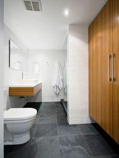 Modern Bathroom Design: slate grey floor tiles, white subway wall tiles, wood accents