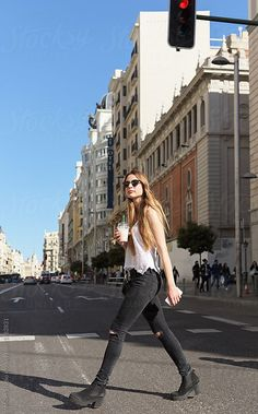 Stylish girl walking on street by Milles Studio for Stocksy United Young trendy woman in sunglasses holding cup of drink and crossing street confidently.