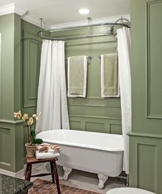 The master bath was enlarged by stealing space from an adjacent hallway for an alcove with a vintage claw-foot tub and new moldings. | Photo: Mark Lohman  Paint (walls): False Cypress, @behrpaint Towel and scrub brush: @pier1imports