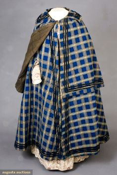 LADYS BLUE PLAID WINTER CLOAK, 1840-1860 November, 2007 -Tasha Tudor Historic Costume Collection New Hope, PA Wool twill in blue, brown and cream plaid, hand stitched, large turn down collar above half cape, all with three rows narrow black velvet ribbon around collar, cape and hem, two pocket slits under cape, brown cotton lining, wool batting, three hooks & eyes, (wear to velvet ribbon, lining damaged at neck) excellent.
