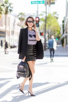 Model and fashion blogger Alexandra Lapp wearing an MCM backpack, high waist mini skirt in black leather with silver buckles from Manokhi Leather, white linen striped zipped top from Karl Lagerfeld, with a leather sunglasses application, Dior Slingback pumps in black patent calfskin leather and J'Adior ribbon with a 10 cm heel, Dior choker around the neck, Diormania sunglasses by Dior, Saint Laurent jacket and the Dual Stark Cyber backpack from MCM with techno-graphic details, made from…