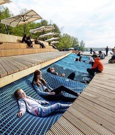 WEBSTA @ designboom - netting for relaxing interrupts the wooden boardwalk of this public project by RS architects in poland allowing residents to lie, sit and socialise while facing the lake.#designboom #architecture