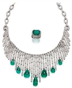 A stylish necklace from the 1920s, designed to evoke a waterfall. It is set with circular-cut diamonds suspending seven cabochon emerald drops. The ring, probably by Boivin, has a step-cut emerald within an articulated bezel set with a fringe of baguette diamonds, 1930s. Courtesy Sotheby's.