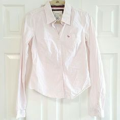Abercrombie & Fitch Striped Button Down .top is 98% cotton 2% spandex. Button-down longsleeve light pink striped shirt with seven buttons down the front 2 button on each cuff. Good condition. gently washed and worn. No rips or stains. Abercrombie & Fitch Tops Button Down Shirts